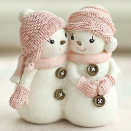 Two snowmen in a knitted hat, scarf and mittens